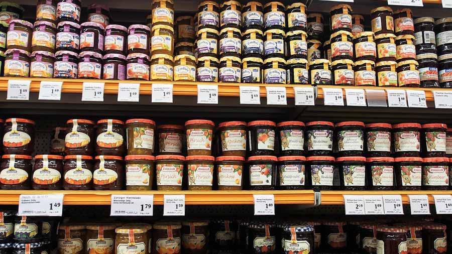 scaffale del supermercato con confetture e marmellate con differente etichetta